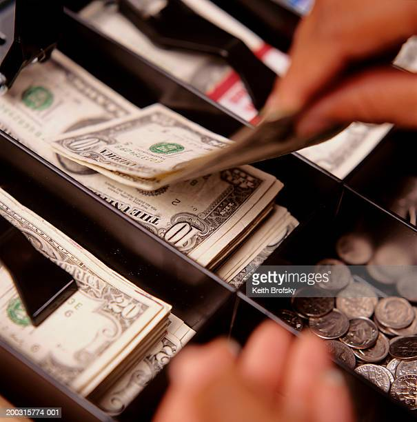 Person taking money from cash register, close-up