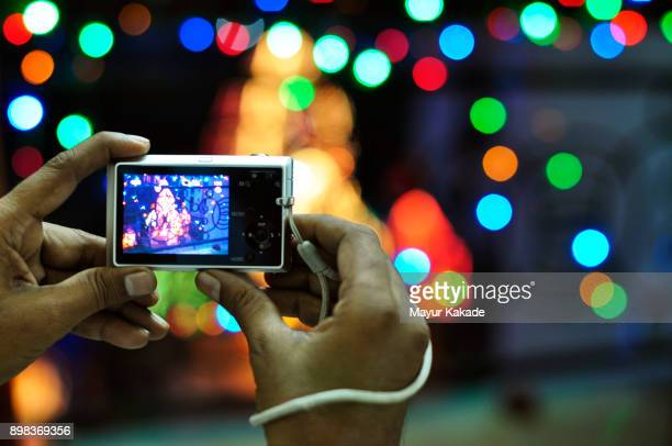 Person Taking Picture of Temple and Festive lighting