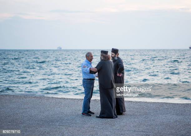 person talking to religious people at coast of Thessaloniki greece
