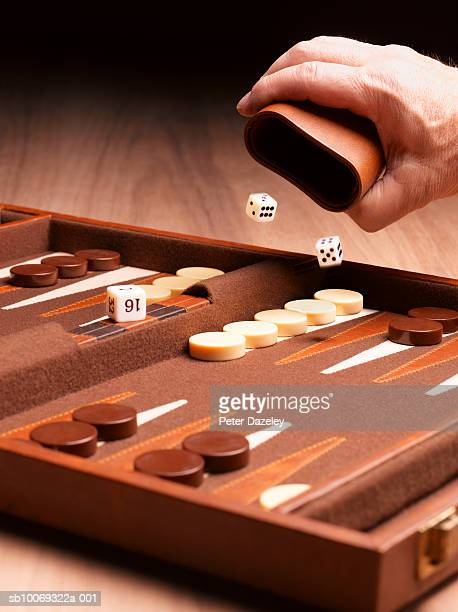 person throwing dice on backgammon board, studio shot - バックギャモン ストックフォトと画像