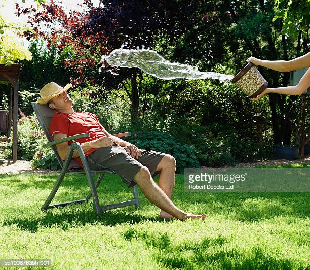 Person throwing water out of bucket on man sleeping on deck chair in garden