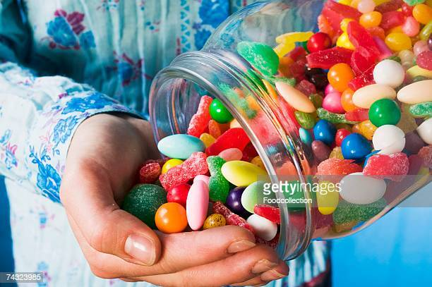 Person tipping sweets out of jar