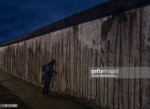 Person touches a segment of the Berlin wall at the Bernauerstrasse wall memorial on the 30th anniversary of the fall of the Berlin Wall, on November...