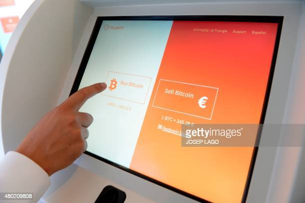 A person touches the screen of a bitcoin ATM of Bitchain Spanish company in a shopping center in Barcelona on July 10 2015 Bitchain Spanish company...