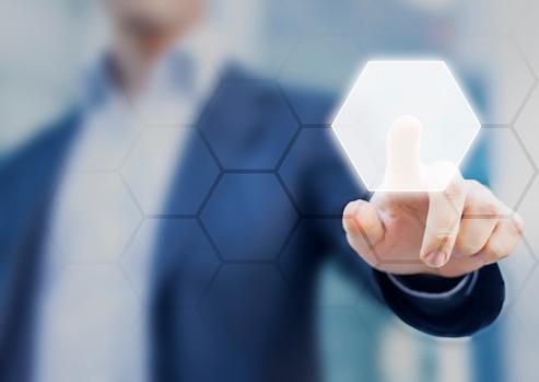 Person touching an hexagonal button on a digital interface 610122106