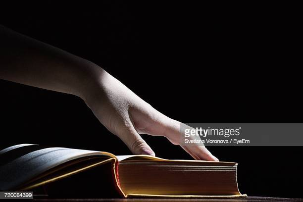 Person Touching Book Against Black Background