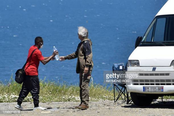 Person travelling in a campervan gives a bottle of water to a young migrant who has just crossed the Franco-Spanish border as he makes his way...