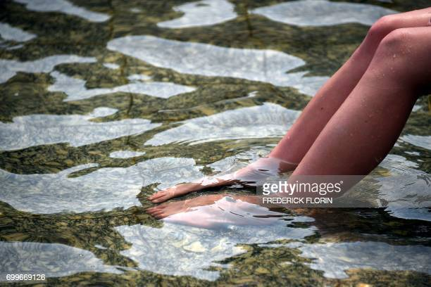 A person tries to cool off in a fountain in Strasbourg northeastern France on June 22 as temperatures climb across Europe Europe continued to sizzle...