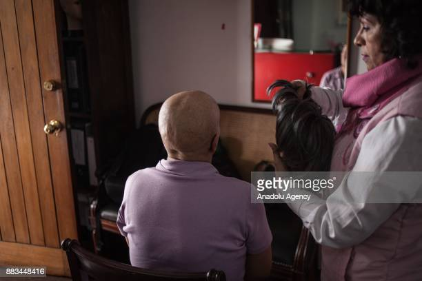 A person trying different options at the bank of wigs at the AMESE Foundation who help victims with cancer to find an opportunity at the essential in...