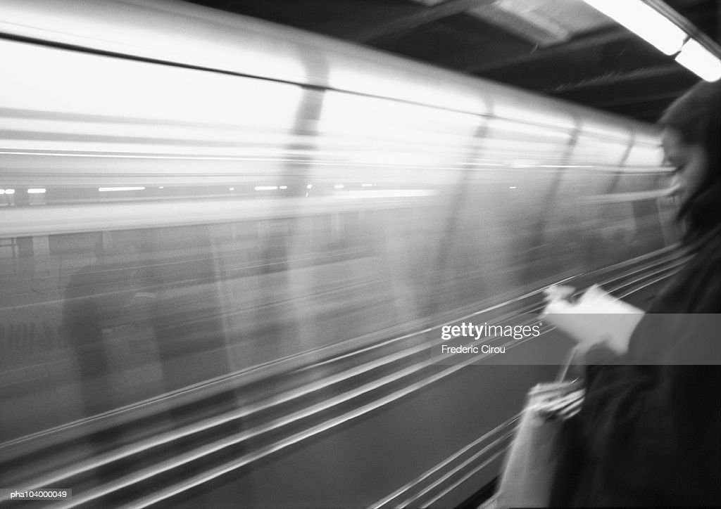Person under neon light standing by passing subway train, blurred, b&w : Stockfoto
