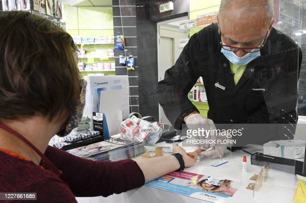 Person undergoes a finger prick blood sample as part of of an antibody rapid serological test for COVID-19 from a pharmacist in Strasbourg, eastern...
