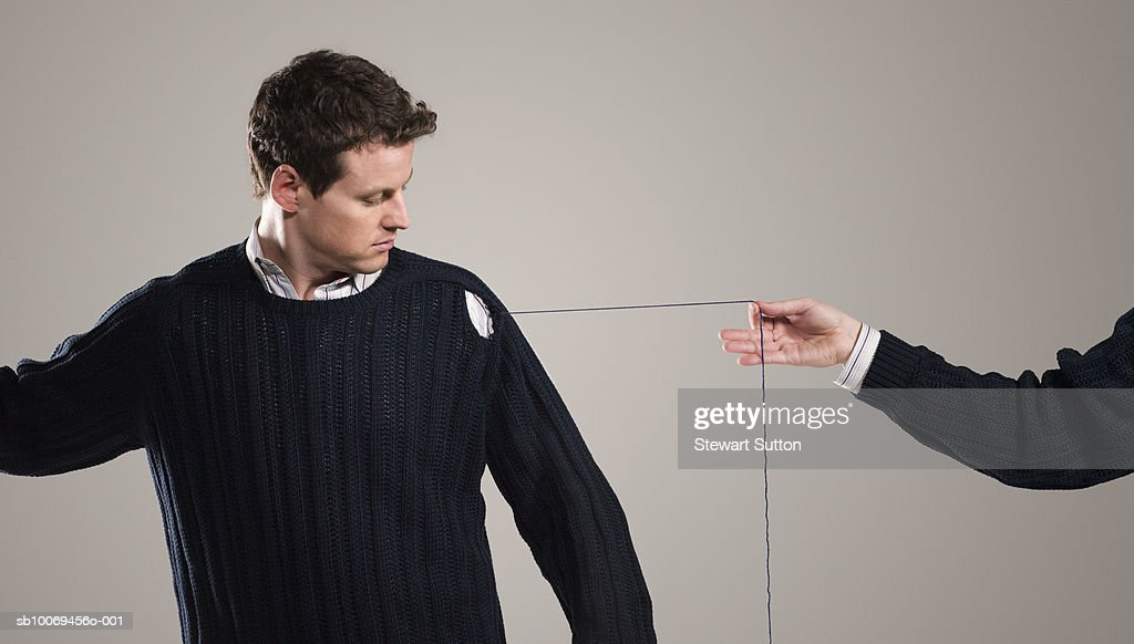 Person unraveling mans sweater, indoors : Stock Photo