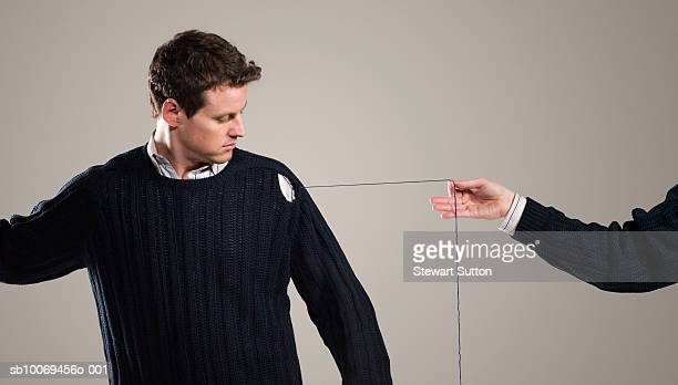 person unraveling mans sweater, indoors - lã - fotografias e filmes do acervo