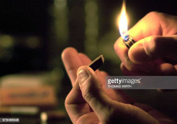 A person uses a cigarette lighter to heat a piece of cannabis resin to mix the substance with tobacco to prepare a hashish joint 01 December 2001 in...