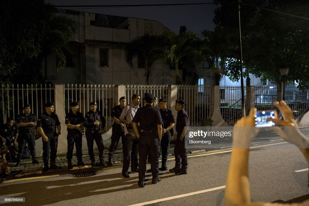 A person uses a mobile device to take a photograph of police officers standing outside the residence of Najib Razak, Malaysia's former prime minister, in Kuala Lumpur, Malaysia, on Thursday, May 17, 2018. Malaysia's Prime Minister Mahathir Mohamad said he wouldn't cut a deal with Najib if any wrongdoing was found in a corruption probe into state fund 1MDB. Najib has repeatedly denied wrongdoing after 2015 revelations that around $700 million -- alleged to be 1MDB funds -- appeared in his personal accounts before the prior election in 2013. Photographer: Sanjit Das/Bloomberg via Getty Images