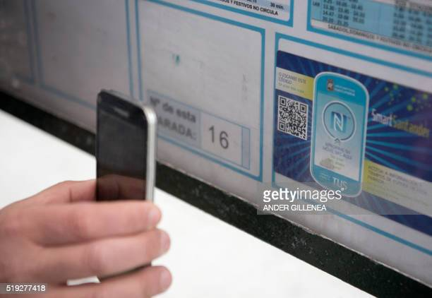 A person uses a mobile phone to read a QR code or 'smart sticker' on a public bus stop in the northern Spanish city of Santander on March 16 2016 In...