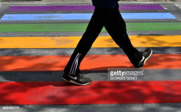Person uses a road crossing adorned with the colours of the rainbow in Perigueux on May 17, 2018 as part of events marking International Day against...