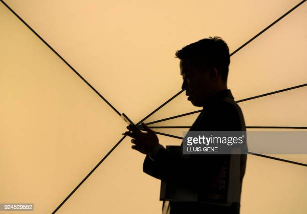 TOPSHOT A person uses a smartphone at the Mobile World Congress the world's biggest mobile fair on February 26 2018 in Barcelona The Mobile World...