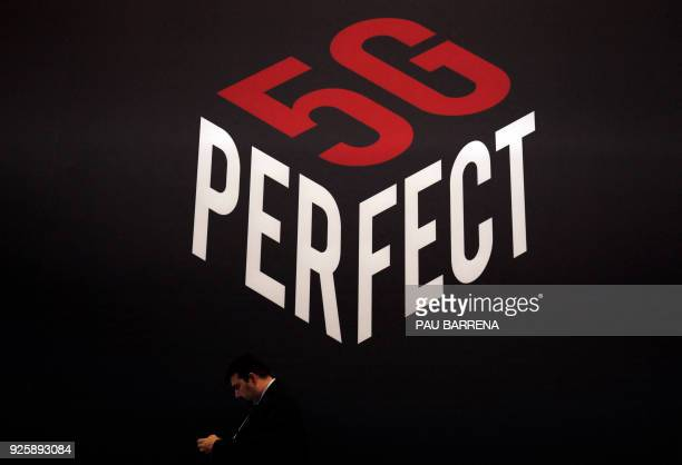 A person uses a smartphone under a 5G Perfect logo at the Mobile World Congress on the last day of the world's biggest mobile fair on March 1 2018 in...