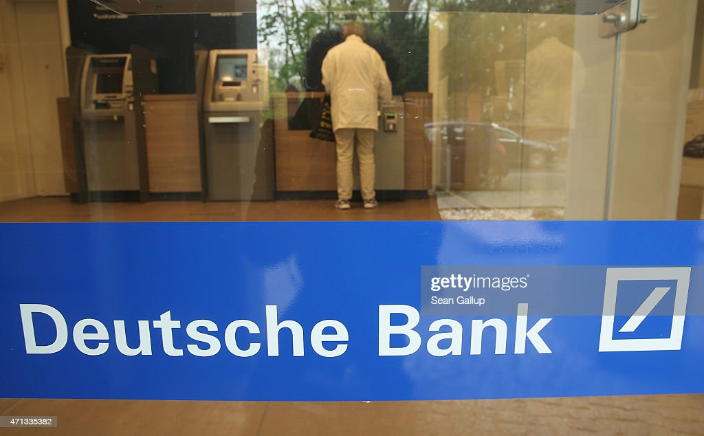 A person uses an automated banking machine at a branch of German bank Deutsche Bank on April 27, 2015 in Berlin, Germany. Deutsche Bank announced earlier in the day that it will close 200 of its 700 branches in Germany over the next two years in an effort to save an annual EUR 3.5 billion.