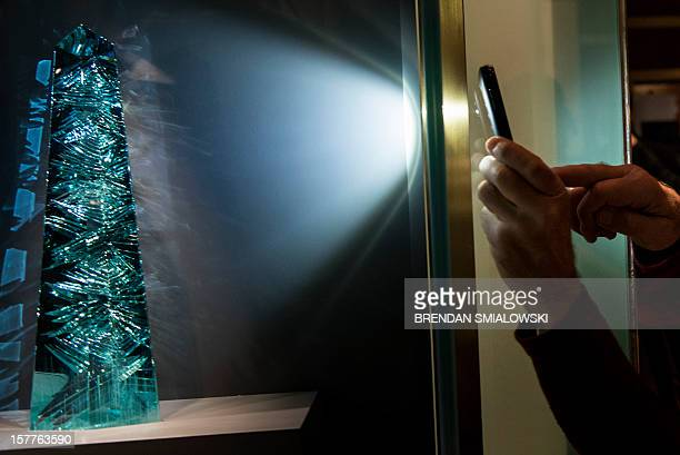 A person uses an iPhone to photograph the Dom Pedro after its unveiling in the Janet Annenberg Hooker Hall of Geology Gems and Minerals at the...