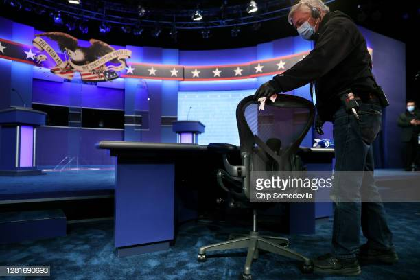 Person uses disinfecting wipes to clean the chair that will be used by NBC News' Kristen Welker during the second presidential debate at the Curb...
