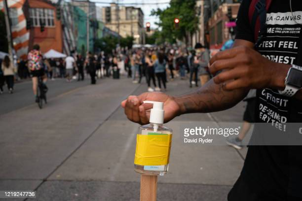 """Person uses free hand sanitizer in the so-called """"Capitol Hill Autonomous Zone"""" on June 10, 2020 in Seattle, Washington. The zone includes the blocks..."""