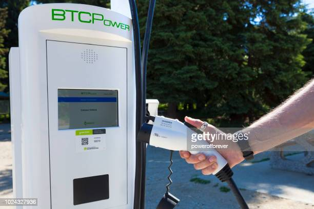 Person Using a BTCPower Electric Car Charging Station