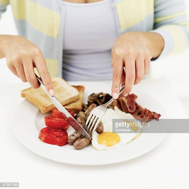 Person using a fork and knife on a plate with eggs bacon and sausages