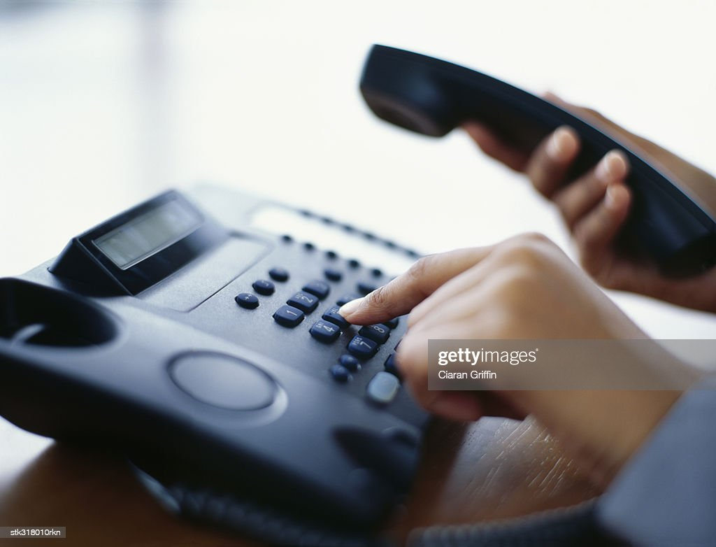 person using a landline phone in an office : Stock Photo