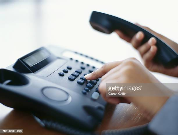 person using a landline phone in an office