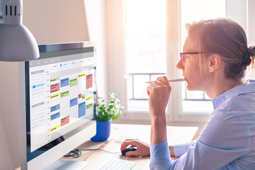 Person using calendar on computer to improve time management, plan appointments, events, tasks and meetings efficiently, improve productivity, organize week day and work hours, business woman, office 1091264670