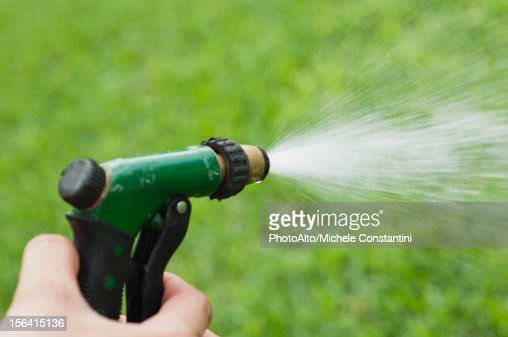 Hose Spray Nozzle >> Person Using Spray Nozzle On Garden Hose To Water Lawn Cropped Stock Photo - Getty Images