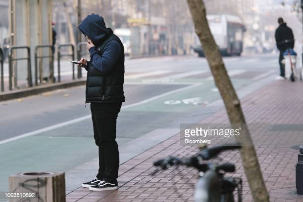 A person views a mobile device near Twitter Inc headquarters in San Francisco California US on Thursday Nov 15 2018 Most tech stocks have been...