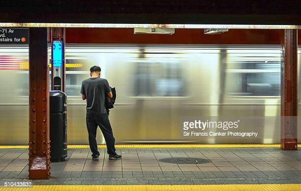 Person waiting as a metro train passes by at high speed