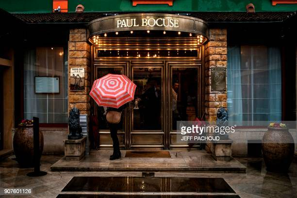 TOPSHOT A person waits at the entrance to the restaurant of French chef Paul Bocuse restaurant 'L'auberge du Pont de Collonges' on January 20 2018 in...
