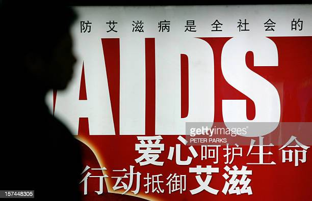 A person waits for a train in front of an AIDS awareness poster in a Beijing subway station 25 January 2006 China is in the grip of a worseniing...