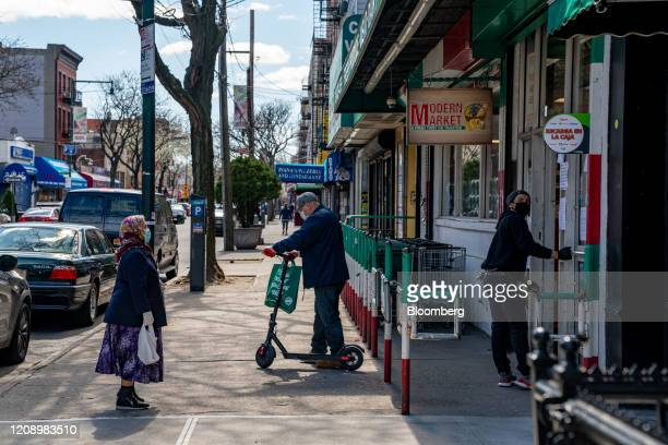 Person waits to enter a supermarket in the Little Italy neighborhood in the Bronx borough of New York, U.S., on Thursday, April 2, 2020. In four...