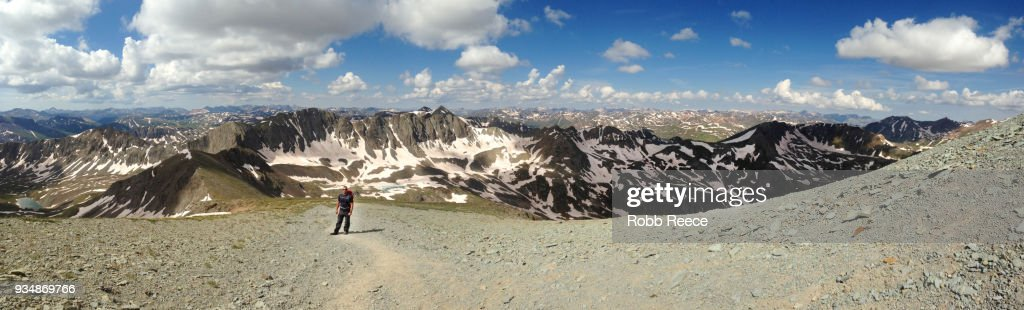 A person walking alone on a high, remote mountain trail : Stock Photo