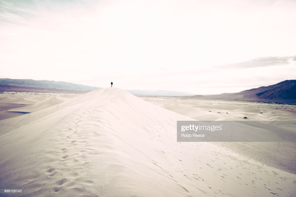 A person walking alone on a remote sand dune : Stock Photo
