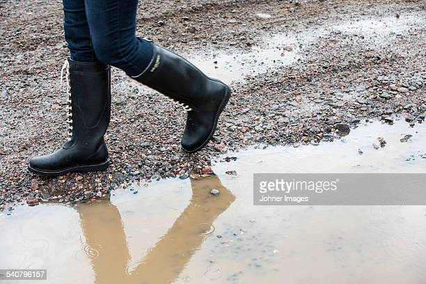 Person walking along puddle, low section