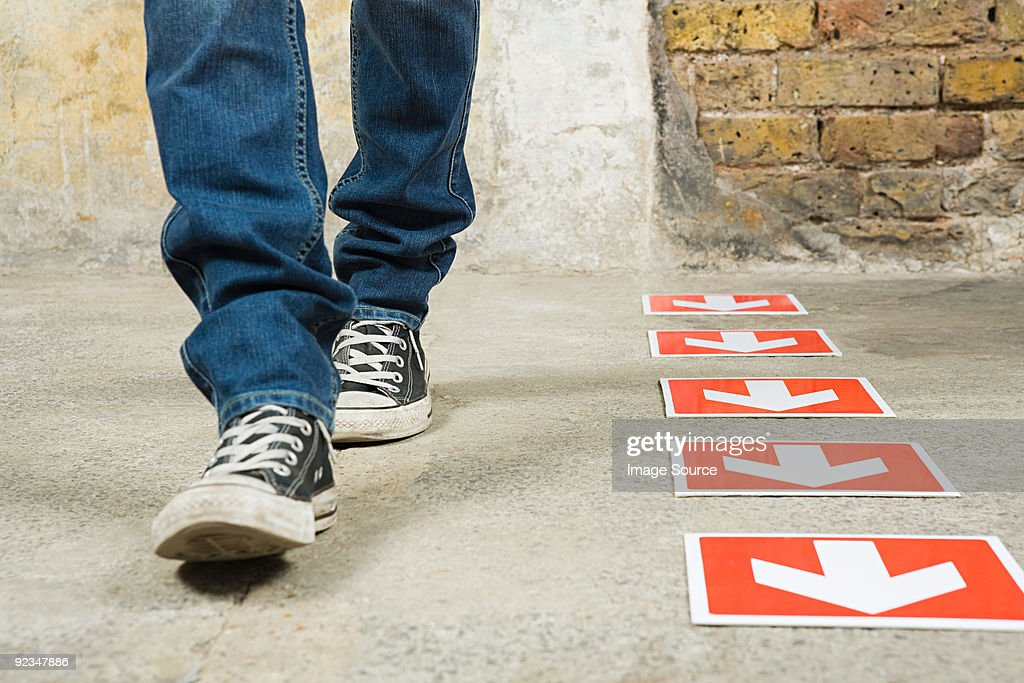 Person walking by arrows : Stock Photo