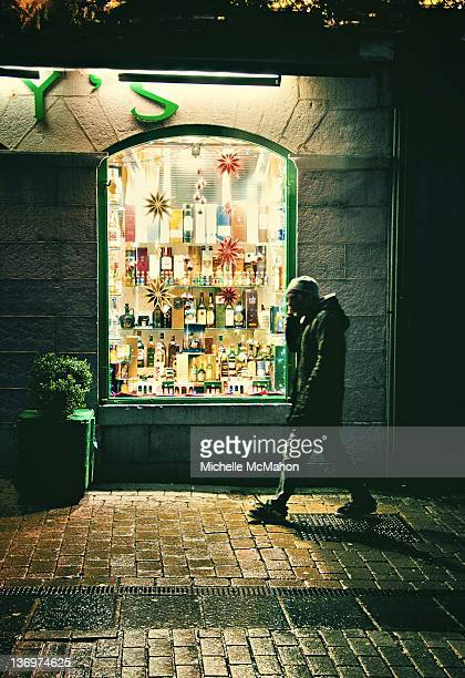 Person walking by window wine shop