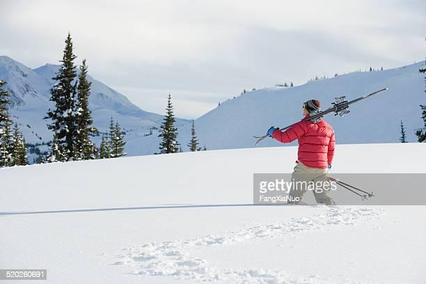 Person zu Fuß in knietiefen Pulverschnee Ski auf der Schulter
