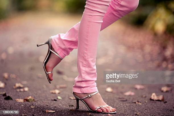 Person walking in pink jeans and high heels