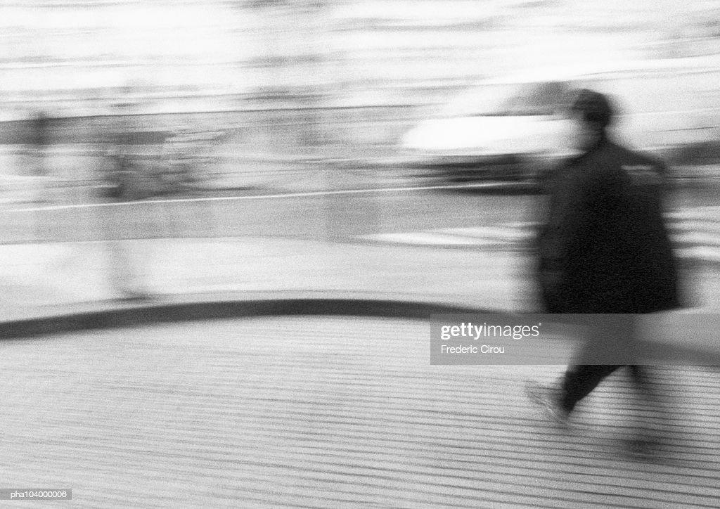 Person walking in street, blurred, b&w : Stockfoto