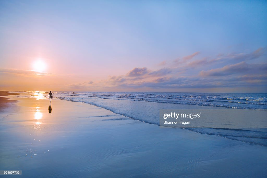 Person walking on beach at sunrise : Stock Photo