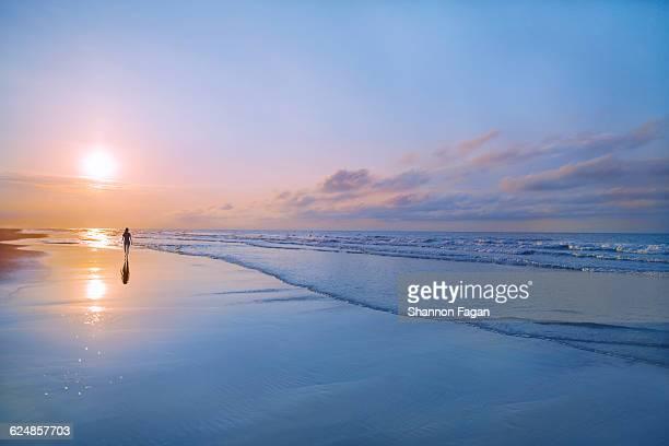 person walking on beach at sunrise - cena de tranquilidade imagens e fotografias de stock