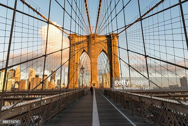 person walking on brooklyn bridge walkway at morning - brooklyn bridge stock pictures, royalty-free photos & images