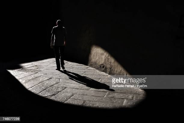 person walking on dark street - pedestrian walkway stock pictures, royalty-free photos & images